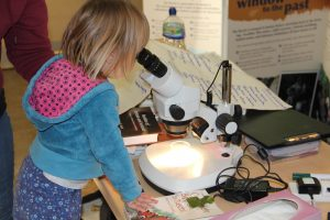 A young girl looking through a microscope