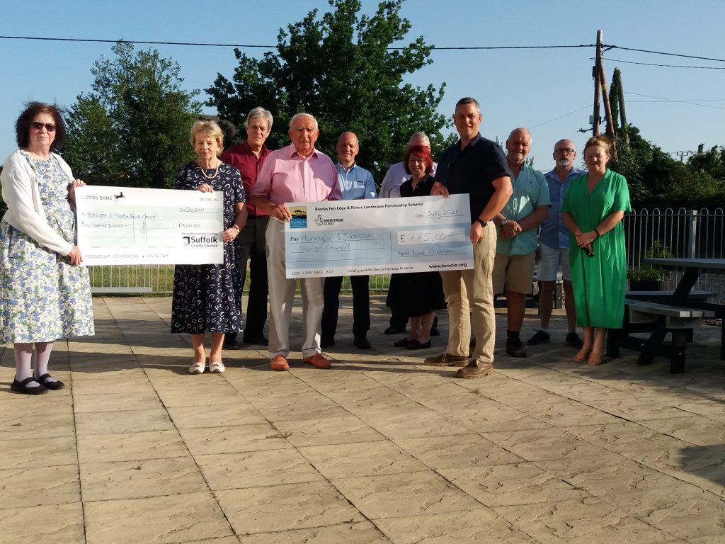 Suffolk County Councillor Joanna Spicer, and Nick Dickson from the Brecks Fen Edge & Rivers Landscape Partnership present cheques to Rob Williams and Linda Howe of Honington and Sapiston Parish Council in support of a new series of Heritage interpretation boards celebrating the rich history of the Parish.