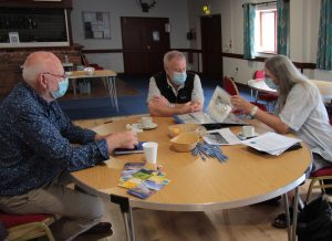 Volunteers round a table researching